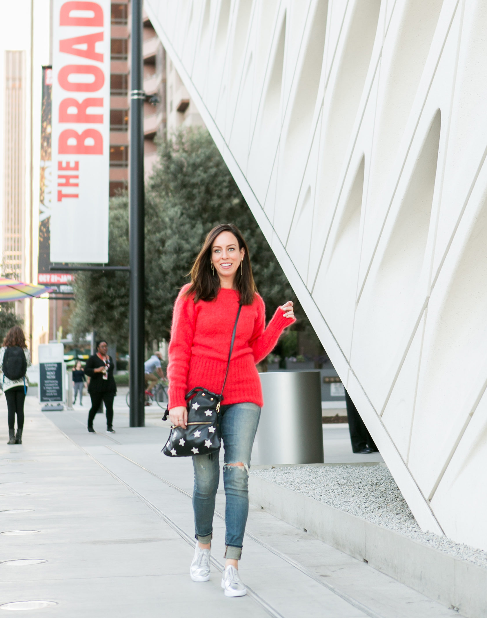 Sydne Style shows what to wear to the broad museum in red sweater and jeans